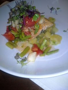 Lemon pepper salmon served with a plantain cubes topped with a heirloom tomato salad