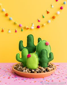 No green thumb required with this cute cactus family! To DIY: 1. Cut out front and back of cactus shape. 2. Sew together with a 1/4 in. seam. 3. Stuff cactus and insert dowel rod. 4. Insert other end of dowel rod into styrofoam (in the saucer). 5. Cover with river stones.