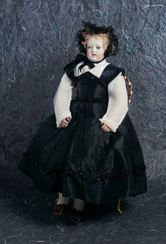 "A beautiful French bisque poupee with painted teeth by Adelaide Calixte Huret, circa 1855. The modeled teeth version of the Huret poupee is extremely rare; this is believed to be the only existing example. The poupee has been a blue ribbon award winner and was featured on the cover of Doll News of UFDC in Spring 1997. The doll was presented in the Theriault's 2003 auction ""Lady Dolls of the 19th Century"" in Newport Beach, CA."