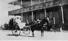 Part of the front of the Salt Water Creek Hotel is shown with wooden stairs, and verandas on two levels. A couple are seated in a buggy in front of the hotel. Horse And Buggy, Wooden Stairs, Salt And Water, New Zealand, Entrance, The Outsiders, Australia, Horses, 1920s