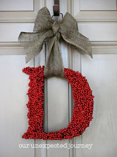 DIY Monogram Wreath. Cheap mdf letter from Michaels, glue gun, holly from Michaels and burlap garland or ribbon. Just cut the holly off and glue! Fill in the spaces and you're done! Depending on the letter of your last name you may have to get creative with how you hang your ribbon from the letter. LOVE.