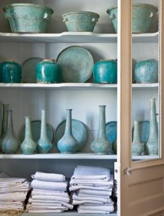 Vintage turquoise plates, urns and bottles in a French armoire