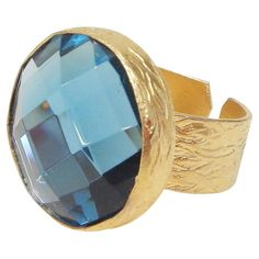 Add a touch of glamour to your ensembles with this chic cocktail ring, showcasing a faceted glass gem in aqua and brushed gold-plated accents.