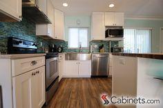 L-shaped white Shaker kitchen with coastal accents like multi-colored blue/green backsplash.