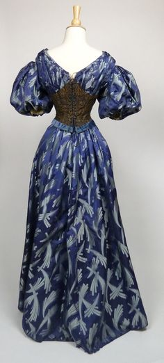 "Blue silk brocade gown with matching day and evening bodices c. 1900.  Blue silk with pale blue abstract design.  Hight neck bodice with beadwork and center front covered button closure.  Evening bodice with short puffed sleeves and lace up back closure.  Slight train to the skirt.    Label (evening bodice waistband):  ""Mrs Robinson 36 Seymour Street Liverpool"""