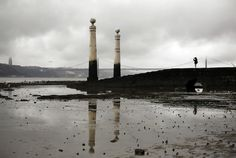 A young man takes photos by the Tagus river at low tide, in Lisbon, May 8, 2012. (Francisco Seco/Associated Press)