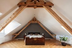 Loft bedroom with visible timber roof trusses, and a patterned parquet floor