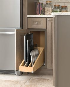 Whether your dinners are three-Michelin-stars-worthy, or you're still learning the ropes, if you spend a lot of time in the kitchen, these storage and organization ideas are for you!Trays That StayA roll-out tray divider helps keep baking sheets and trays upright for easy access. No more having to dig out that cookie sheet that is (of course) at the bottom of the heap!