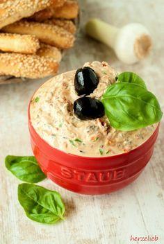 Für das Rezept für den mediterranen Dip braucht ihr Frischkäse, getrockneten Tomaten, Basilikum und schwarzen Oliven. Die Brotstangen sind schnell gebacken.