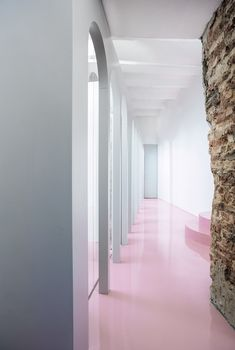 Office design by Crosby Studios. Raw office with feminine pink floors. Eames office chair white. Grey designer sofa. Exposed bricks. Concrete. Bookshelf.