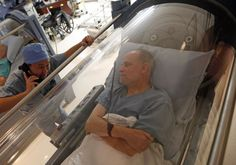 Doctor Andy Chiou (L) speaks to patient Carl Dolson in a hyperbaric chamber in Peoria, Illinois Photo By: REUTERS