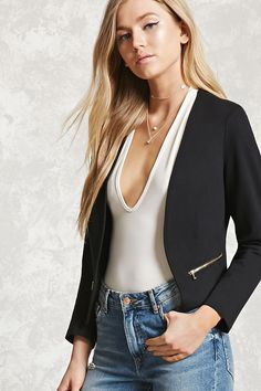 A knit blazer featuring an open front, mock high-polish zippered pockets, long sleeves, and a reverse high-low hem.