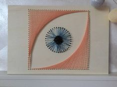A large blue eye made in string art, the base of the picture is made of natural wood. An original and unique decoration for your home or studio! Our creations are all handmade with the string art technique. String art is a passion we have since children, at the beginning we did