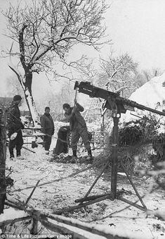Soldiers of US 1st Army hacking at frozen ground to dig foxholes near their machine gun position.