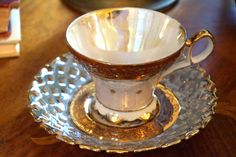 Vintage Royal Halsey fine china cup and saucer by Lipper & Mann - circa 1950s. Very unusual design with an open lace cut-out pattern in the saucer. This set has a luster iridescent finish with gold tr