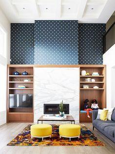 Built-in bookshelves, marble fireplace, and polka dot wallpaper