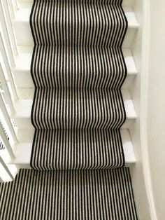 Funky black and white stair Runner with black edges fitted onto white wooden stairs