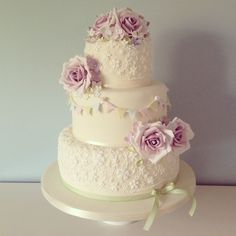 A beautiful three tier ivory wedding cake, finished with delicate hand made vintage roses, pretty bunting and intricate lace design. From The Pretty Cake Company. www.theprettycakecompany.com