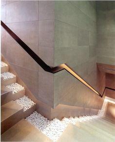 Ein modernes Design für die Treppe mit Kieselsteinen und Geländer in der Wand