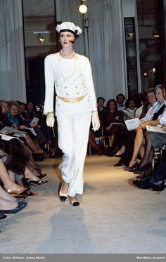 Modevisning. Modell i vit jacka med gulddetaljer, vita byxor, pösig hatt, handskar och accessoarer. Från Chanel.