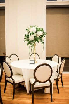 Tall centerpieces white hydrangea, mums and roses with greenery on gold candle sticks