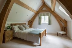 Border Oak - Dramatic oak cruck frame and vaulted ceiling in a cottage bedoom.