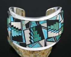 Cuff | Tommy Jackson (Navajo).  Sterling silver with an inlay of fossilized ivory from Alaska, blue-green Royston turquoise from Nevada and old Blue Gem turquoise separated by sterling strips and accented with black jade.