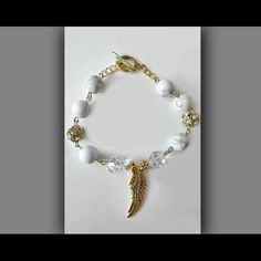 Angel Wing Bracelet in Gold with Swarovski Crystal Handmade in USA. This luxuriously stylish bracelet comes fully equipped with gold metal connection. The all natural white gemstone rounds matched with the gold rhinestone accents and genuine Swarovski crystals make this bracelet a truly unique design. Classic toggle clasp closure for a secure fit. Crystalz & Co. Jewelry Bracelets
