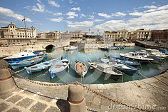 Port of Syracuse, Sicily (Italy), Some ships standing. Historic buildings on the horizon. Sky and clouds.
