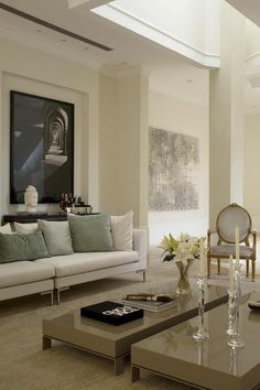 Love the neutral sofa with the green cushions, dark artwork and antique chair.  Just love this space.