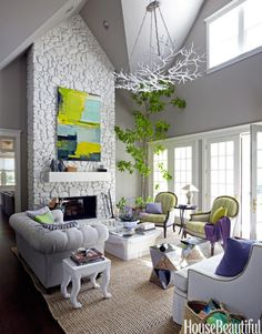 In the living room of a house in California wine country, designer Stephen Shubel painted the stone fireplace and Currey & Company's Rainforest chandelier a powdery white.
