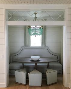 A doorway with transom window leads to a dining nook filled with a gray Greek key dining banquette accented with brass nailhead trim facing a gray wash oval dining table lined with triangle shaped stools illuminated by a turquoise beaded chandelier, Ro Sham Beaux Fiona Chandelier.