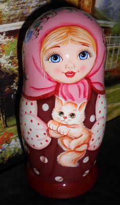 Belos olhos azuis. Matryoshka (boneca russa) segurando um gatinho.