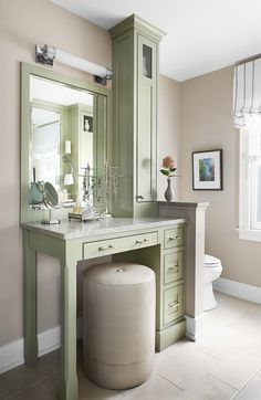 A custom vanity is the highlight of this bathroom. Pale sage green is the perfect understated color to pair with the low-profile beige walls. #bathroomideas #bathroomcolorschemes #beigebathrooms #bathroomdecor #remodel #bhg