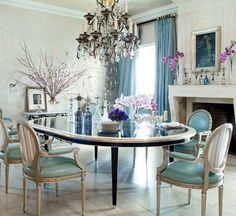 The Directoire-style fireplace in the dining room of Ozzy and Sharon Osbourne's home, designed by Martyn Lawrence Bullard, is from Exquisite Surfaces, and the table and chairs are by Martyn Lawrence-Bullard Design...