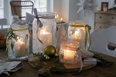 Glass jars with frost effect and ribbons on Christmas table