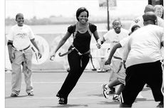 Michelle Obama plays flag football with children and former NFL players and coaches during her Let's Move campaign to fight childhood obesity. She once urged the food industry to make healthier products for kids and is now focusing on exercise to combat obesity.