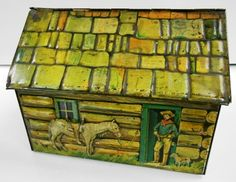 """BISCUIT TIN LOG CABIN. Circa 1920's. Embossed tin shingled roof and log sides. Can't read all the print on bottom but it appears to be Robertson's biscuit tin. Measures 6 1/2"""" in length X 5"""" in width X 4 3/4"""" in height."""