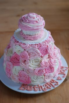 sweet girl's 1st birthday cake! Love the mini cupcake on top for the birthday girl...so clever!