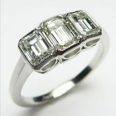 English Triplets: Direct from London, this fantastically refined ring features a charming array of emerald cut diamonds set in sleek bezels with sophisticated arched detail in the under gallery.  English, ca.1950.  Maloys.com