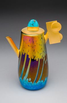 """Teapot of blown and iridized glass with lid, handle and spout of 24 karat gold over sterling silver. Lid holds a matrix turquoise. 7"""" tall"""