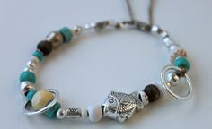 item #B052 Swimming around- is a cute bracelet that is made with a beautiful silver fish charm surrounded by wooden beads, vintage african beads, silver rings, pukas, silver plated beads, clear and turquoise glass beads all on a natural cord.