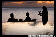 POLINESIA. COOK ISLAND: Aitutaki. Isla Cook. Polinesia. El sur del Océano Pacífico. Una camarera sirve deliciosos cócteles en la playa en el lujoso Hotel Pacific Resort Aitutaki.