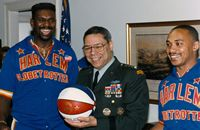 1991-Globetrotters honor Joint Chiefs of Staff Chairman Colin Powell with official uniform and game ball at the Pentagon.