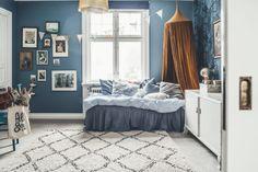 Kids room with vintage decor and blue walls and wallpaper by Krickelin. Photo: Kristin Lagerquist Barnrum med vintage inredning, sänghimmel, kelim och tavelvägg.