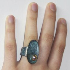 """Anillo """"perla"""" ovalado. Pieza realizada en latón, soldada con plata y acabada con pátina de cobre y lacado al horno. Anillo abierto universal (2,8 cm de ancho máximo y 5,5 cm de largo)."""