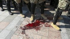 "Interior ministry officers stand next to a pool of blood outside the parliament building in Kiev, Ukraine, August 31, 2015. At least four police and national guard were badly hurt when a grenade was lobbed from a crowd of nationalists demonstrating outside parliament against the ""decentralization"" draft law that President Petro Poroshenko and his government are pushing as part of a blueprint to end separatist rebellion in the east. REUTERS/Valentyn Ogirenko"