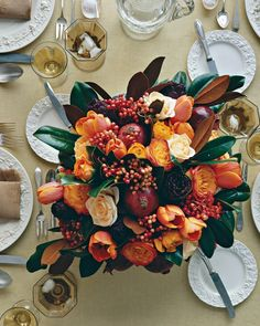 A Thanksgiving table demands a feast for the eyes with all the trimmings. But bear in mind that well-mannered centerpieces should never block guests' views of one another. A low container is just what's needed, leaving room for lavish helpings of pomegranates, red viburnum berries, tulips, roses, and ranunculus served up with a bronzy-green magnolia-leaf wreath.
