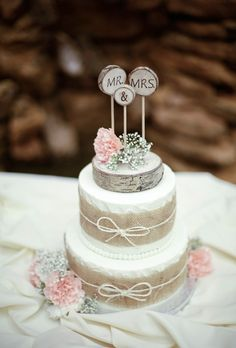 Two-Tiered Cake with Burlap Ribbon. For a rustic bash, The Crown Room designed a two-tiered confection, made of marble cake with cookies-and-cream filling. Burlap and twine bows adorn the white cake, plus pale pink-and-white flowers.
