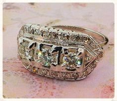 """A fabulous estate ring with remarkable versatility: a lady could wear this piece as """"simply"""" a ring or as an engagement or wedding ring.  Made in 14k white gold, it centers on three old European cut diamonds (0.70cttw), which are surrounded by a border of diamond melee.  Circa 1936. Total diamond weight = 0 .95cttw."""